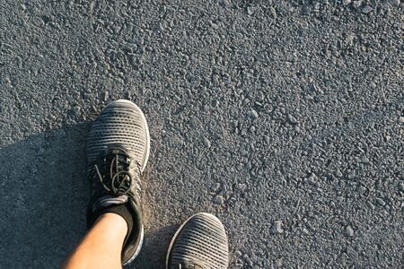 Closeup people walking with gray shoes on road in park for health concept. 写真素材