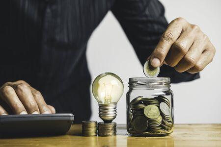 Geschäftsmann hält Glühbirne auf dem Schreibtisch im Büro und schreibt auf Notizbuch es für Finanz-, Rechnungswesen, Energie, Ideenkonzept. Standard-Bild