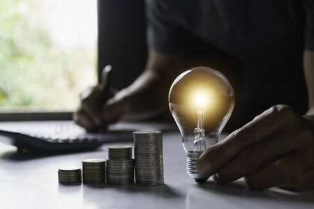 Business man holding light bulb on the desk in office and writing on note book it for financial,accounting,energy,idea concept.