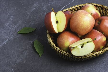 Group of apples and sliced in basket put on table and with leaves beside. Фото со стока
