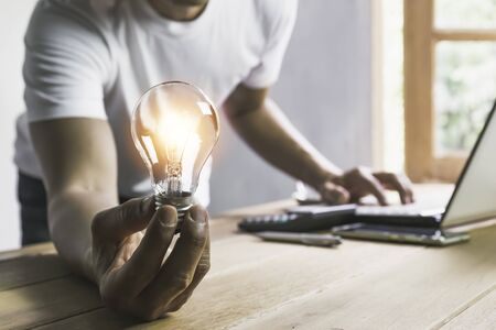 Business man holding light bulb on the desk in office and using  computer in  financial,accounting,energy,idea concept.