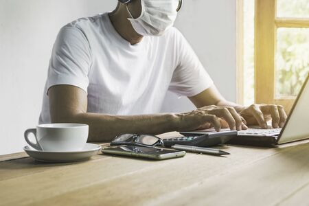 Man working at home in covid 19 virus situation and using laptop on table also wearing a mask for safety. Фото со стока