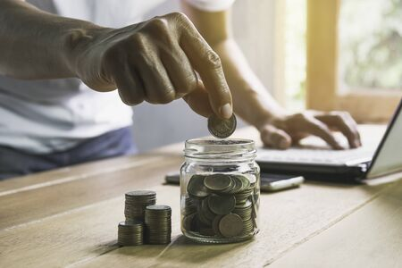 Men are using laptop about save money and put coin in glass jar on desk on table in the office. Фото со стока