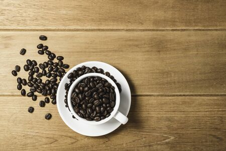 Top view flat lay coffee bean in cup on wooden.