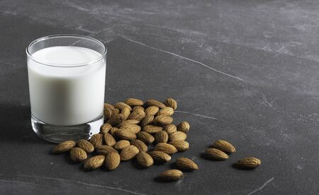 Close up glass of milk with almonds nut on table.