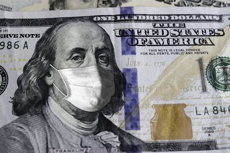 One Hundred US.Dollar bill with medical mask safety covid-19 on 2020. Фото со стока