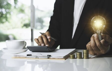 Business man holding light bulb on desk in office and putting calculator with coins or money on work desk also for idea,energy,finance concept. Фото со стока