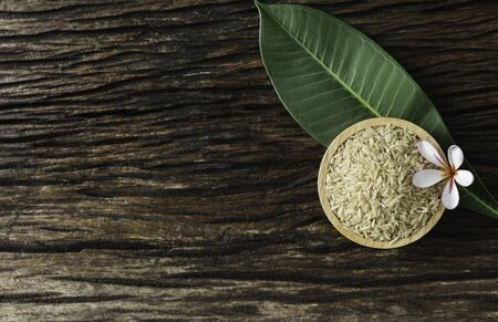 Top view brown rice with leaves tree on wooden.