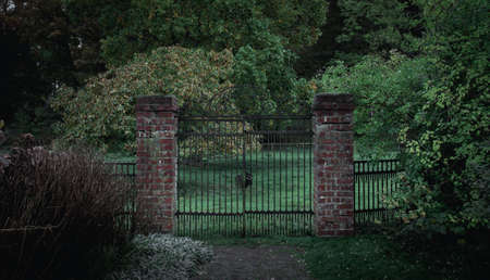 Dark and moody iron gate with brick columns to a mystic garden