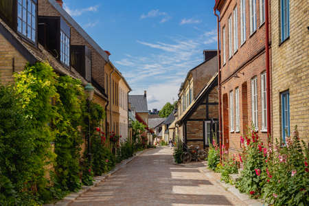 A warm sunny morning in the historic old town of Lund, Sweden. A narrow cobblestoned street bordered with townhouses and half-timbered houses. Archivio Fotografico