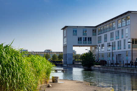 A white apartment building next to a park with reed and water taken on a sunny summer day.