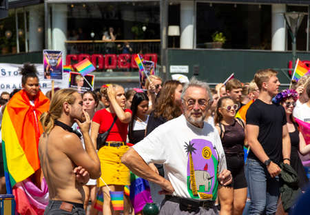Malmö, Sweden - July 20, 2019: An old man and a younger bare chested man both have a troubled look as they participate in the gay pride parade through the citycenter of Malmö, Sweden.