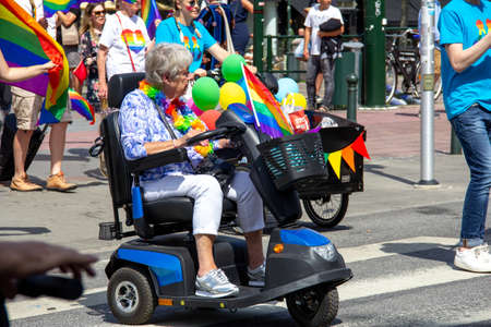 Malmö, Sweden - July 20, 2019: A senior woman on a mobility scooter, decorated with rainbow flags and colors, is participating in the annual pride parade in Malmö, Sweden.