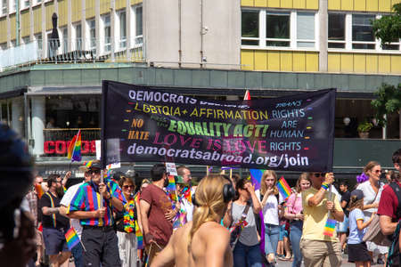 Malmö, Sweden - July 20, 2019: People holding up a banner from Democrats Abroad with messages about love and equality during the annual gay pride parade in Malmö, Sweden.