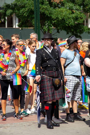 Malmö, Sweden - July 20, 2019: An eccentric man dressed in a Scottish way with kilt and a bowler hat amongst other accessories, as he is taking part in the annual gay pride parade. Publikacyjne