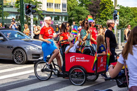 Malmö, Sweden - July 20, 2019: A woman riding a cargo bike with some kids in, painted in the colors of Malmö University, as they participate in the annual pride parade in Malmö, Sweden. Éditoriale