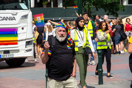 Malmö, Sweden - July 20, 2019: A senior man with grey full beard is waving a pride flag while participating in the annual pride parade in Malmö, Sweden.