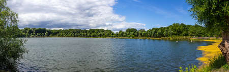 Panoramic view over the lake in the public park Pildammsparken in Malmö, Sweden, during a summer day when clouds are building up on the horizon