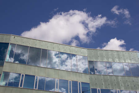 Reflections of the sky and clouds on a modern facade of a building on a summer day