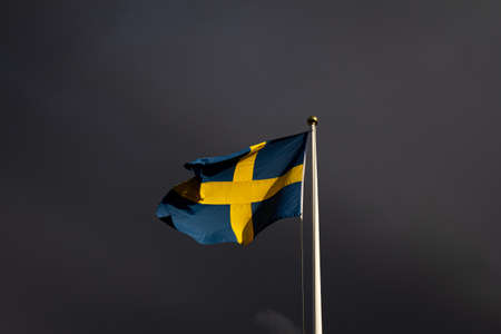 The Swedish flag is waving on a flag pole in the strong winds as a summer storm is making the sky all dark