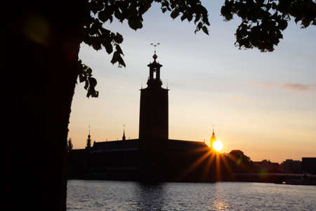 The sun is setting behind Stockholm city hall and the water on a warm summer day in Stockholm, Sweden.