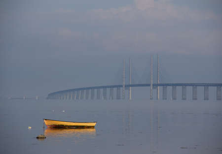 A boat is left lonely in the sea close to the shore while the fog is slowly lifting and revealing the Öresund bridge in the distance on a warm summer morning 版權商用圖片