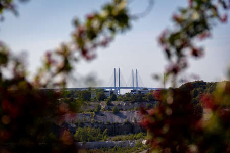 The Oresund bridge is rising above the horizon. Seen from the old limestone quarry, a deep hole in the ground, in Malmö, Sweden