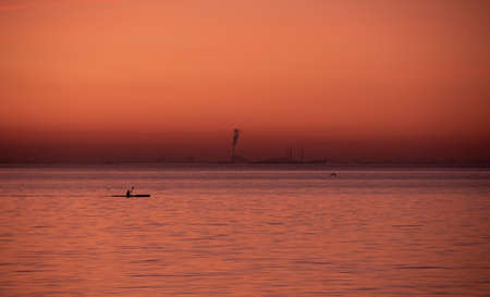 A man is rowing a canoe on the sea while the sky and water is colored in orange and pink during a summer sunset in Malmö, Sweden 免版税图像