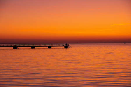 People have walked out on the pier in Malmö, Sweden, while the sun is setting and making the sea and sky all orange and pink.
