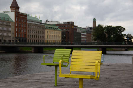The outdoor seats by the canal is empty in downtown Malmö, Sweden, as people stays home during this overcast day Imagens
