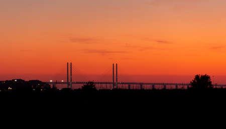The Öresund bridge sunset silhouette during warm summer evening.