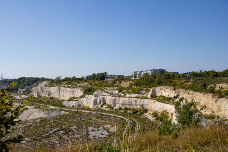 Some buildings stand at the edge of the limestone quarry called Kalkbrottet in Malmö, Sweden. The area is no longer in use, and now a nature reserve