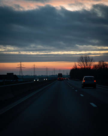 Traffic on the main highway through the landscape of Skåne (Scania) in southern Sweden during a winter sunset.