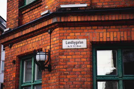 A street sign with the name Landbygatan is mounted on a red brick facade on an old building in the old town of Malmö, Sweden