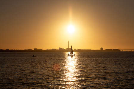A sailboat and a man standing on a surf board is meeting on the sea as silhouettes as the sun sets over Malmö, Sweden Foto de archivo