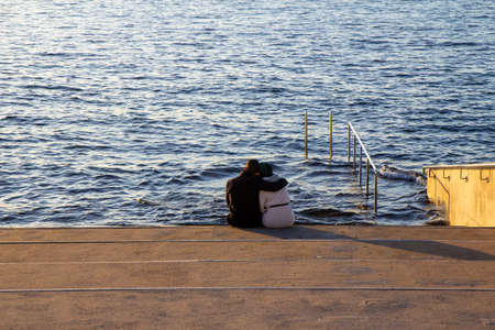 A man is holding his arm around a woman as they sit on a staircase just by the waters edge, looking out to the sea, feeling calm, lonely or sad Foto de archivo