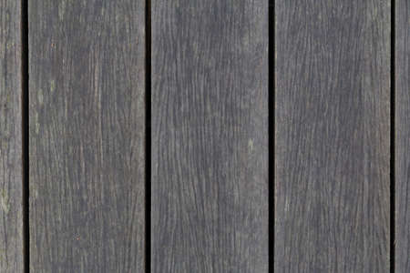 Top down view of grey wooden planks that makes up an outdoor walkway
