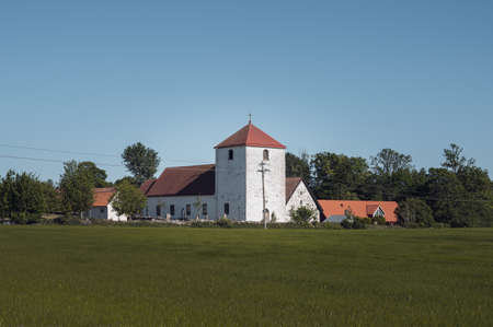 The medieval Fulltofta church stand close to the agricultural fields in the flat farmlands of Skåne (Scania) in southern Sweden Stock Photo