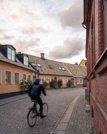 A university student runs his bike along the small cobblestoned streets bordered with colorful houses in the old town of Lund, Sweden