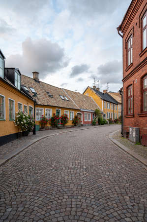 A cobblestoned street bordered with yellow and red townhouses in the historic old town of Lund, Sweden Archivio Fotografico