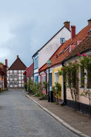 An empty cozy cobblestoned street with multi colored town houses and cottages in the village of Ystad, Sweden Archivio Fotografico