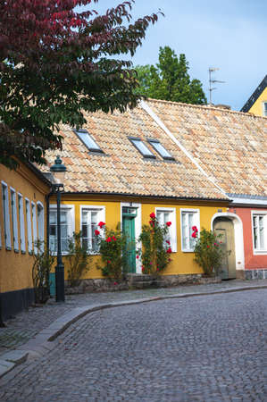 Colorful town houses along a cobblestoned street in the historic medieval old town of Lund Sweden