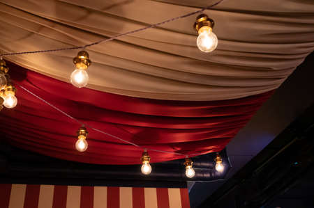 Ceiling decorated with heavy fabrics and light bulbs to show a circus feeling