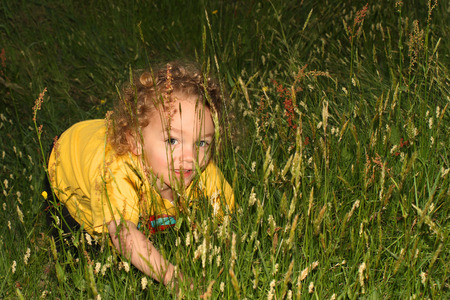 playtime: Child playing in tall grass Stock Photo