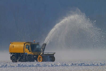 Snowplow removing snow at an airfield Stock Photo