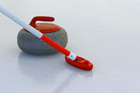 Curling stone and broom on the ice