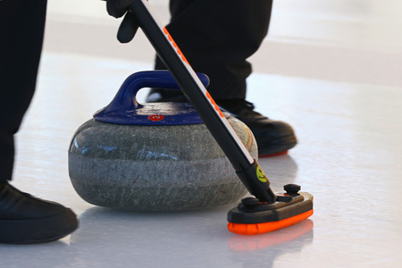 Curling stone sliding down the ice with player's feet running in front of it Stock Photo
