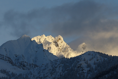 winter storm: Mountain peaks and valley covered in snow with dissipating winter storm clouds and blue skies