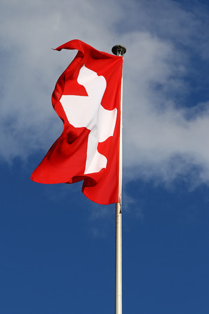 flapping: Flag of the Federal State of Switzerland flapping in the wind against blue skies and white clouds Stock Photo