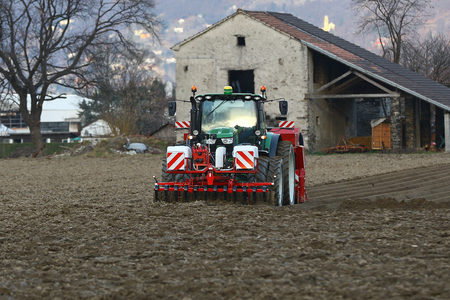 harrowing: Agricultural tractor at work in a field
